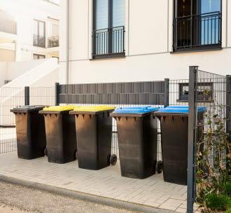 Sorteringskärl för avfall utanför flerfamiljshus. Foto.
